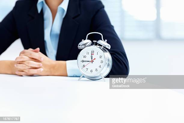 Mid section of a business woman with alarm clock