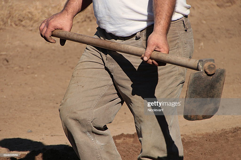 Mid section of a man holding digging hoe : Stock Photo