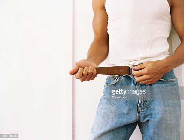 Mid section of a man tying his belt
