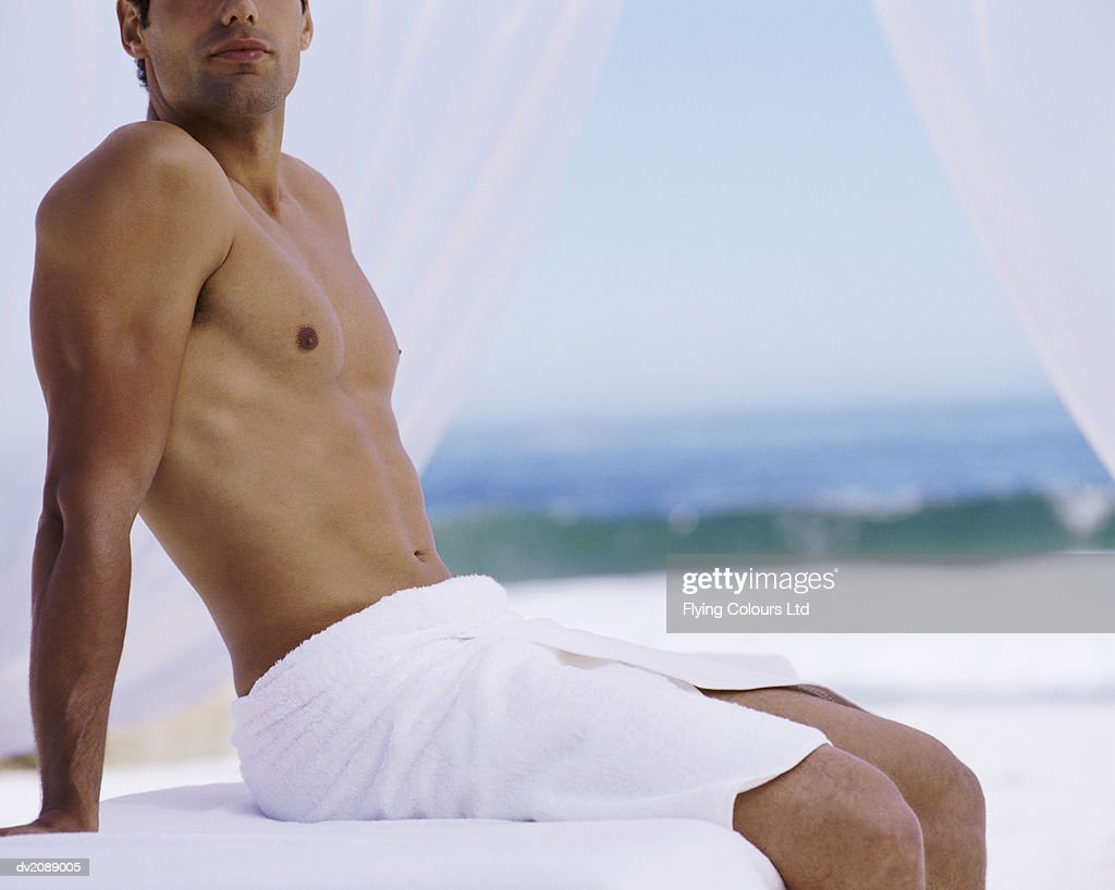 Mid Section of a Tanned, Topless Man Sitting With a Towel Wrapped Around Him : Stock Photo