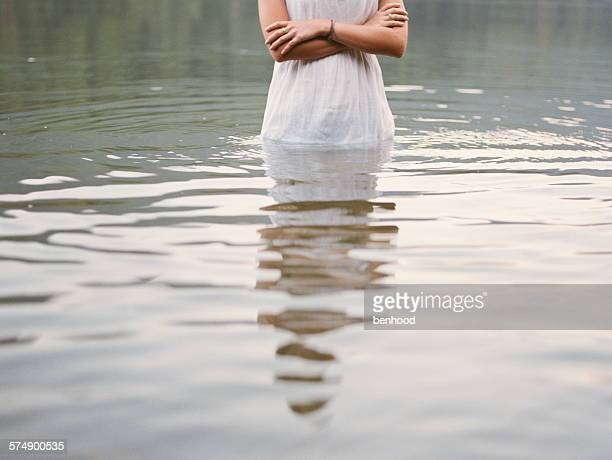 Mid section of a teenage girl in a dress standing in a lake