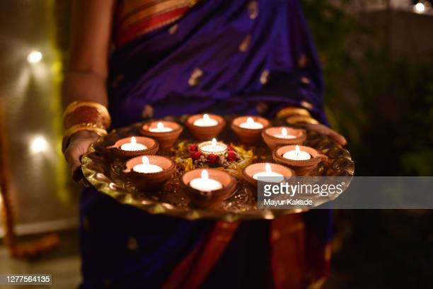 mid section of a woman holding oil lamps - diwali decoration stock pictures, royalty-free photos & images
