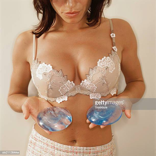 mid section of a woman holding silicone implants