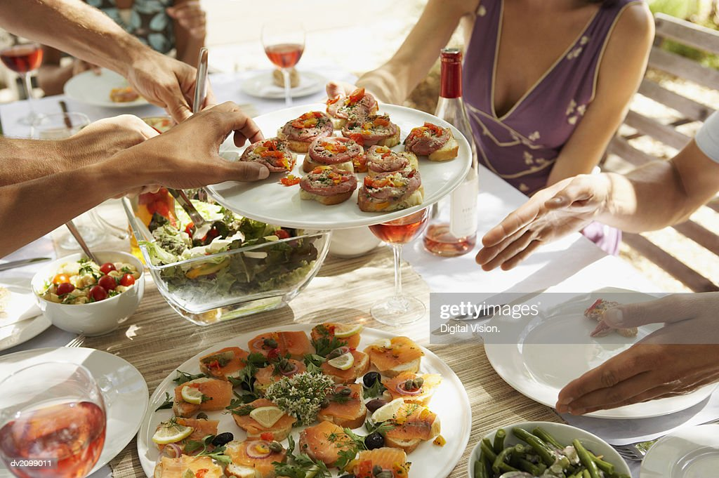 Mid Section of a Woman Passing a Plate of Canapes Around a Table of Men : Stock Photo