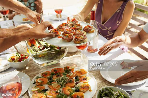 Mid Section of a Woman Passing a Plate of Canapes Around a Table of Men