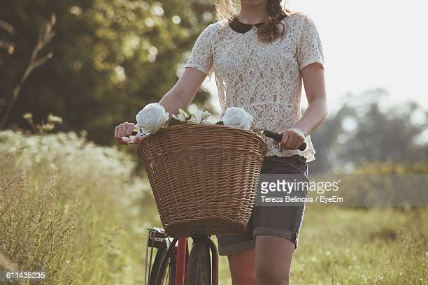 Mid Section Of A Woman With Bicycle On Landscape