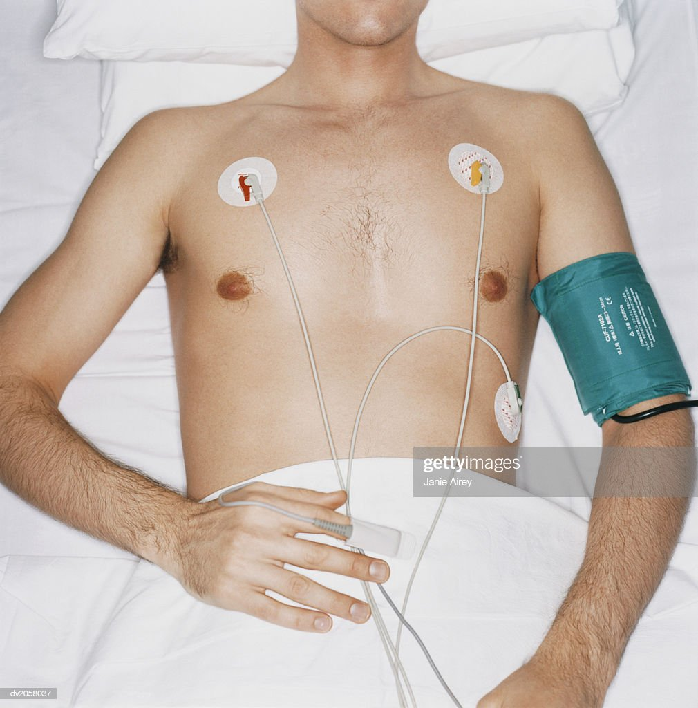 Mid Section of a Young Man Lying in a Hospital Bed With ECG Pads on His Chest : Stock Photo