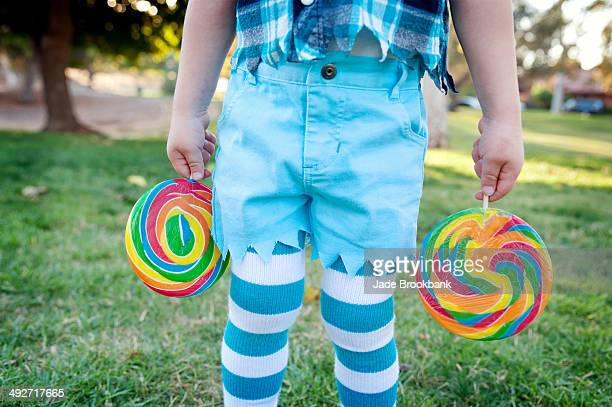 mid section of boy holding lollipops - boys wearing tights stock photos and pictures