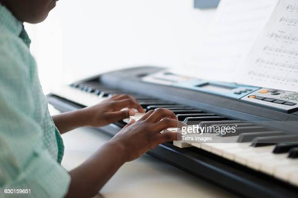 Mid section of boy (6-7) playing keyboard instrument