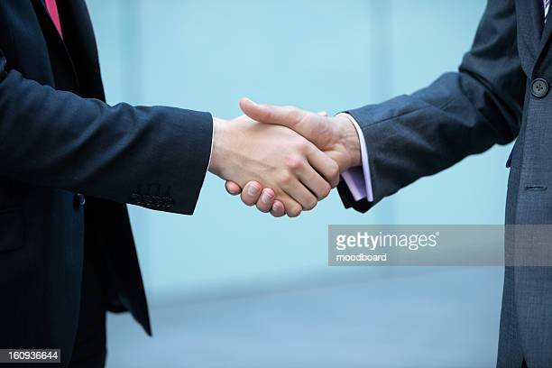 Mid section of business people shaking hands