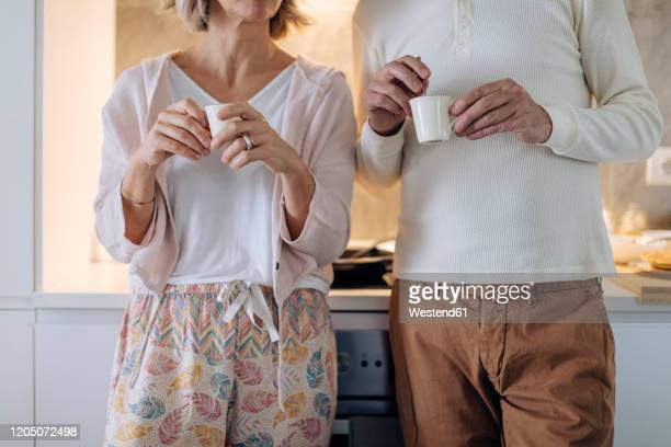 mid section of couple drinking coffee in kitchen at home - heterosexual couple stock pictures, royalty-free photos & images