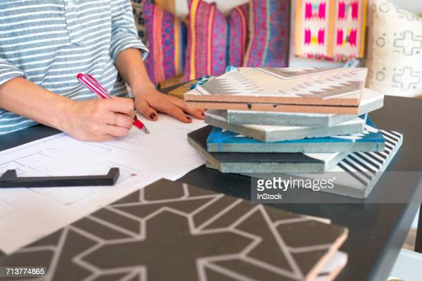 mid section of female interior designer drawing designs at desk in retail studio - interior designer stock pictures, royalty-free photos & images