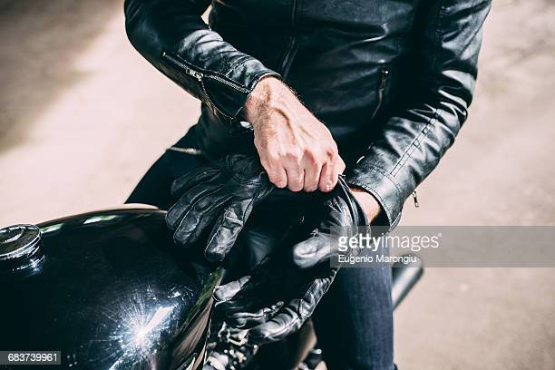 Mid section of male motorcyclist sitting on motorcycle putting on gloves