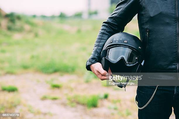 mid section of male motorcyclist standing on wasteland holding helmet - casco protector fotografías e imágenes de stock