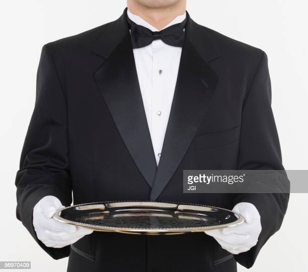 Mid section of male waiter holding tray