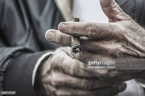 Mid section of man holding cigarette