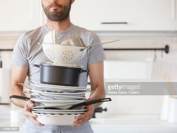 Mid Section Of Man Holding Dishes At Home