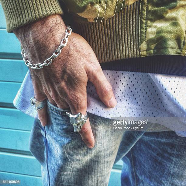 mid section of man with rings and metal bracelet holding hand in pocket - silver trousers stock pictures, royalty-free photos & images