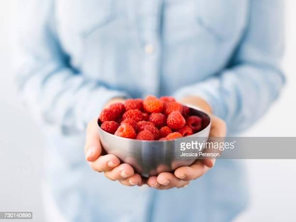 mid section of mature woman holding bowl with raspberries - parte mediana imagens e fotografias de stock