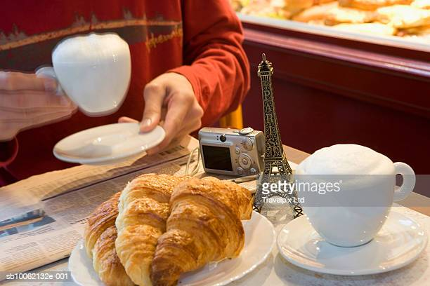 Mid section of person drinking cappuccino in cafe, croissants and Eiffel tower souvenir on table