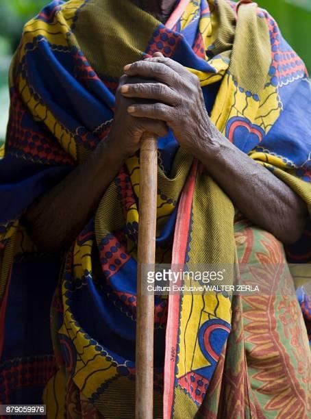 Mid section of person in traditional clothing holding walking stick, Masango, Cibitoke, Burundi, Africa
