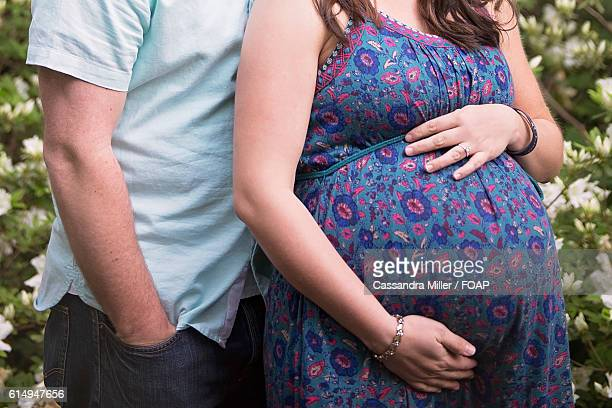 Mid section of pregnant couple standing side by side