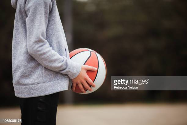 mid section of pre-teen boy holding a basketball on playground