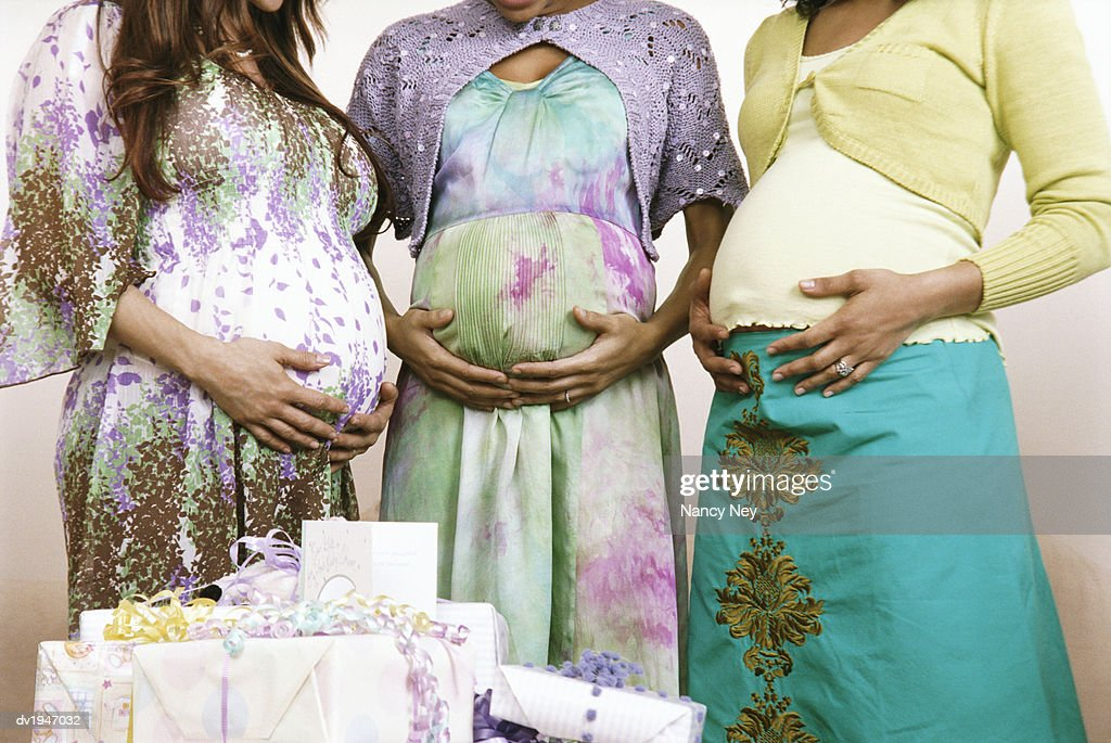Mid Section of Three Pregnant Women Standing by a Pile of Gifts, Holding Their Stomachs : Stock Photo