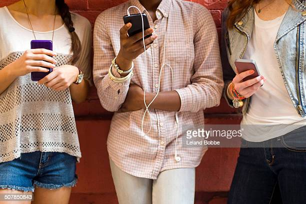 Mid section of three young women using mobile phones