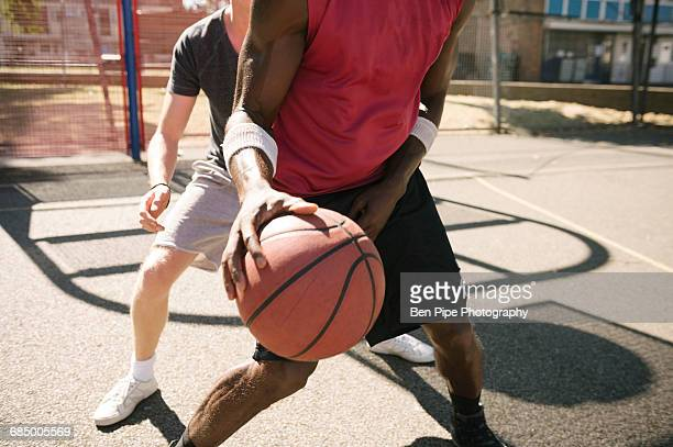 Mid section of two male basketball players practising on basketball court