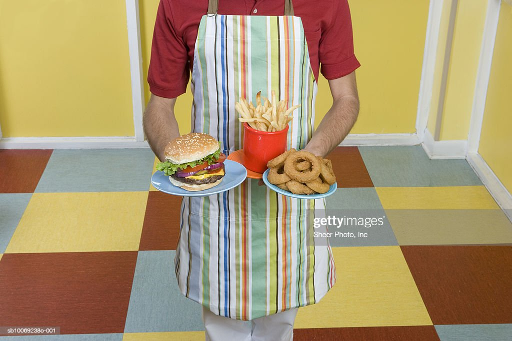 Mid section of waiter holding French fires, hamburger and donuts : Stockfoto