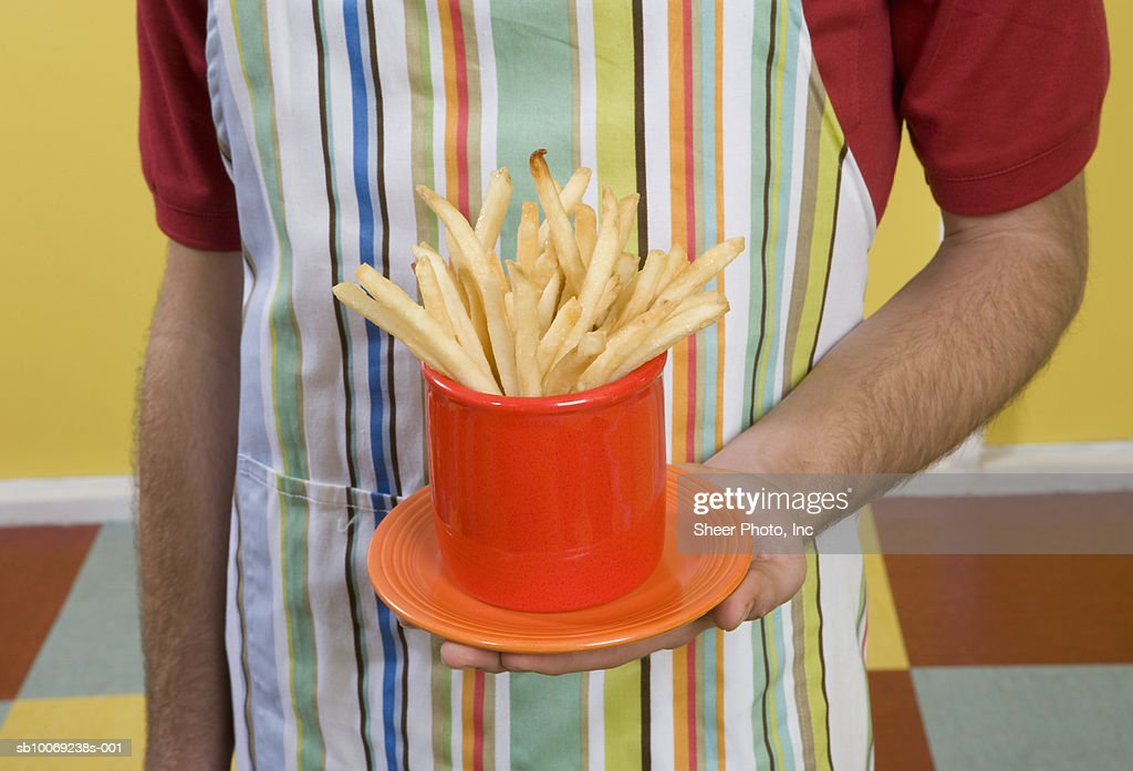 Mid section of waiter holding French fries : Stockfoto