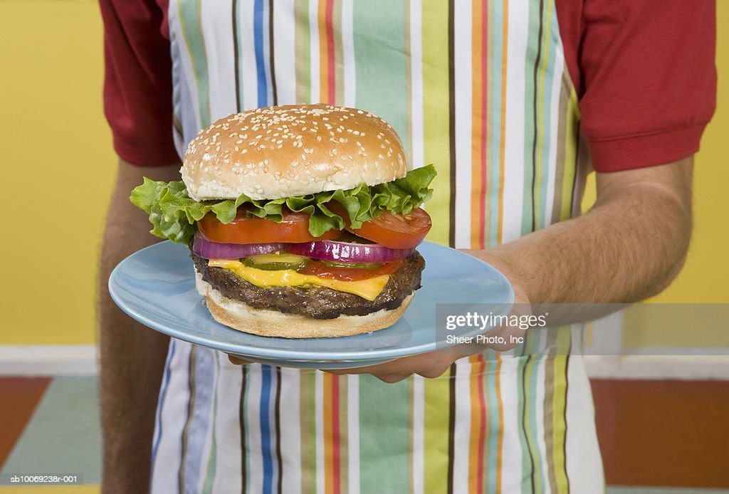 Mid section of waiter holding hamburger : Stockfoto