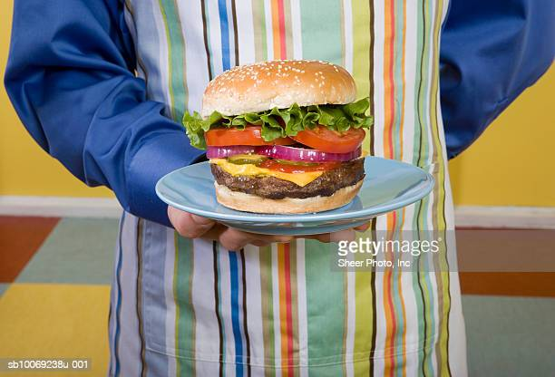 Mid section of waiter holding hamburger