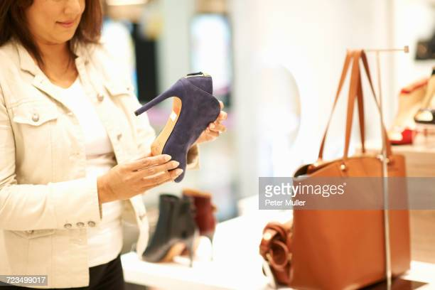 Mid section of woman holding high heeled shoe in shop, Dubai, United Arab Emirates