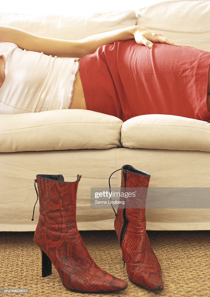 Mid section of woman lying on couch, boots on floor in front. : Stockfoto