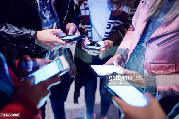 Mid section of young adult friends standing in circle looking at smartphones