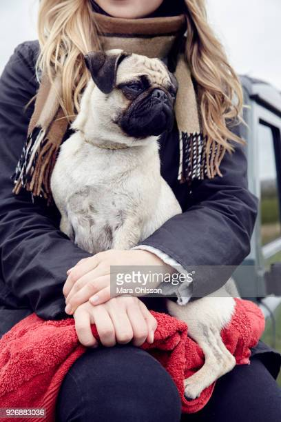 Mid section of young woman sitting on off road vehicle with dog on lap