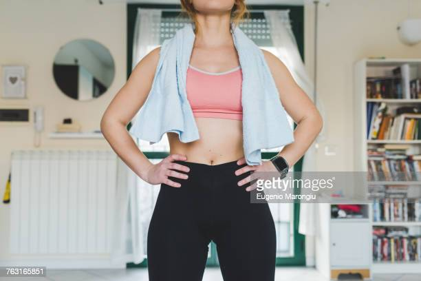 mid section of young woman training, standing with hands on hips - home workout stock pictures, royalty-free photos & images