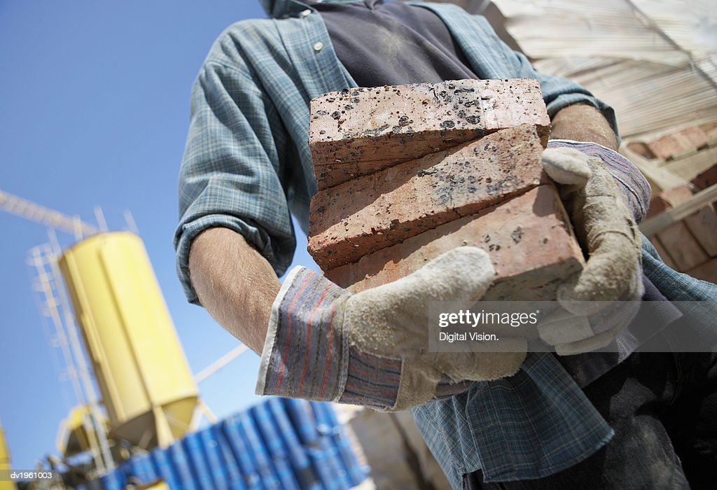Mid Section Shot of a Builder Holding Bricks : Stock Photo