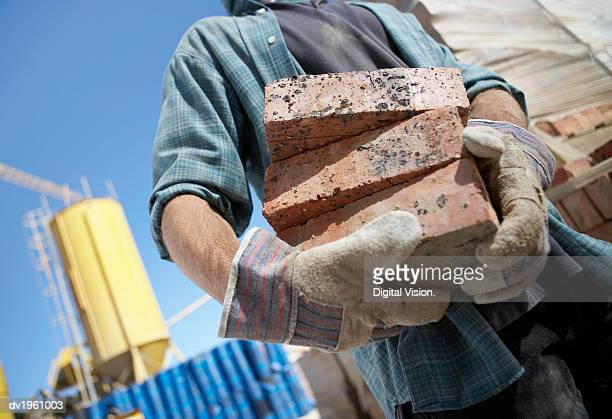 Mid Section Shot of a Builder Holding Bricks