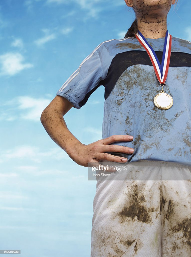 Mid Section Shot of a Mud Splattered Sportswoman Wearing a Gold Medal : Stock Photo