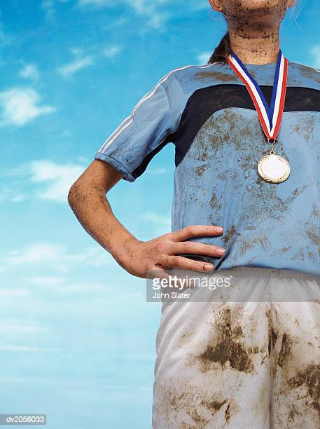 Mid Section Shot of a Mud Splattered Sportswoman Wearing a Gold Medal