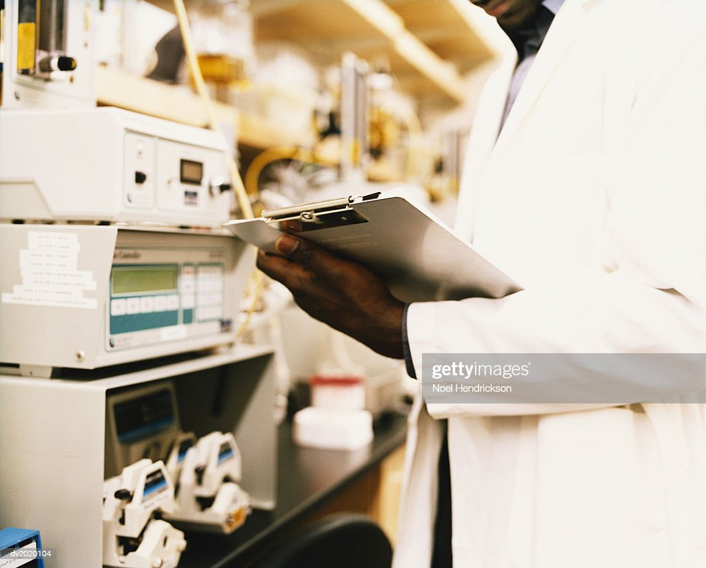 Mid Section Shot of a Scientist Checking a Clipboard : Stock Photo