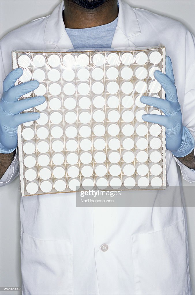 Mid Section Shot of a Scientist Holding a Box Full of Containers : Stock Photo