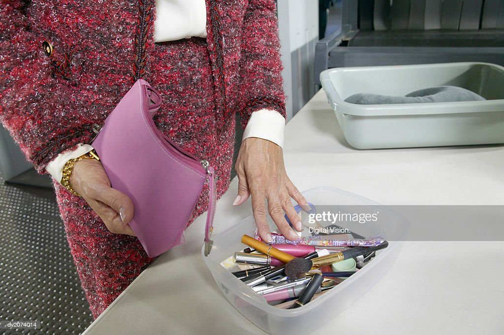 Mid Section Shot of a Woman with a Container Full of Cosmetics at Airport Customs : Stock Photo