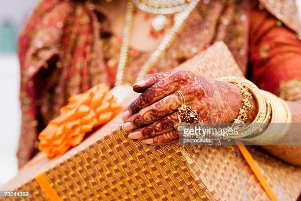 Mid section view of a bride holding a gift