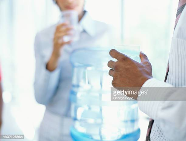 mid section view of a businessman and a businesswoman drinking water in an office