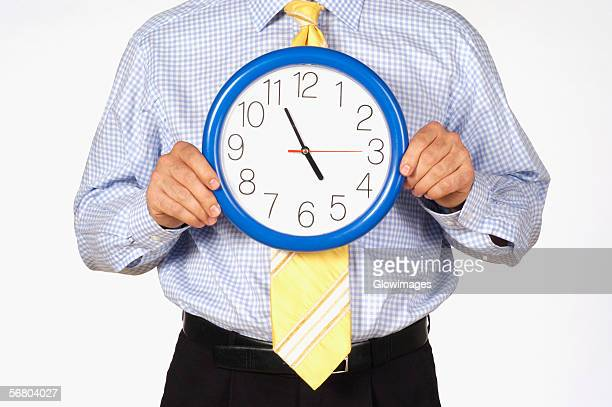 Mid section view of a businessman holding a clock