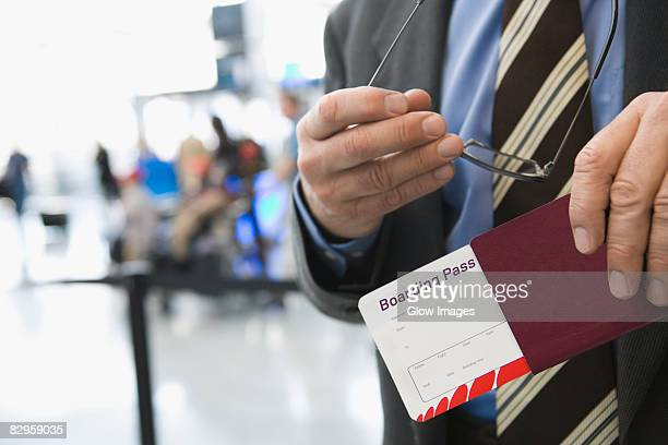 Mid section view of a businessman holding eyeglasses and a passport with an airplane ticket